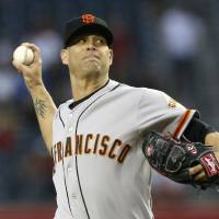 Photo - San Francisco Giants' Tim Hudson throws a pitch against the Arizona Diamondbacks during the first inning of a baseball game, Wednesday, April 2, 2014, in Phoenix. (AP Photo/Ross D. Franklin)