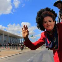 Photo - A demonstrator, wearing a mask in the likeness of Brazil's President Dilma Rousseff, waves from a bus during a protest in front of the Planalto presidential palace, in Brasilia, Brazil, Thursday, July 11, 2013. Tens of thousands of workers across Brazil walked off their jobs on Thursday in a peaceful nationwide strike demanding better working conditions and improved public services. Metalworkers, transportation and construction workers as well as teachers and civil servants adhered to the
