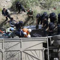 Photo - In this photo released by China's Xinhua News Agency, rescuers try to pull out bodies and survivors from an overturned tour bus after it fell off a 10-meter (30-foot) cliff in Nyemo County, southwest China's mountainous region of Tibet Saturday, Aug. 9, 2014. Xinhua reported the bus carrying about 40 people careened after it crashed in a pileup involving a sports utility vehicle and a pickup truck on a state road. Casualty details were not immediately known. (AP Photo/Xinhua, Chogo) NO SALES
