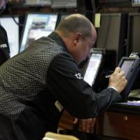 Photo - Trader Christopher Morie works on his handheld device on the floor of the New York Stock Exchange Monday, April 29, 2013. World stock markets were muted Tuesday May 7, 2013 as cheer over the better-than-expected U.S. jobs report faded. (AP Photo/Richard Drew)