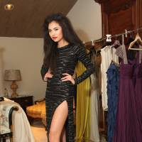 Photo - Before stepping out onto the runway, model Adrianna Standfill shows off a dress for the
