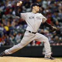 Photo - New York Yankees starting pitcher David Phelps delivers against the Colorado Rockies in the first inning of a baseball game in Denver on Wednesday, May 8, 2013. (AP Photo/David Zalubowski)