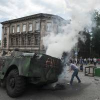 Photo - Local citizens gather around a burning military vehicle at a site of a battle between Ukrainian troops and pro-Russian fighters in Mariupol, eastern Ukraine, Friday, June 13, 2014. Ukraine's interior minister says that government troops have attacked pro-Russian separatists in the southern port of Mariupol. Arsen Avakov said Friday that four government troops were wounded as forces retook buildings occupied by the rebels in the center of the town. (AP Photo/Evgeniy Maloletka)