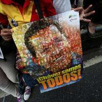 Photo - A supporter of Venezuela's President  Hugo Chavez holds poster of him with the slogan in Spanish