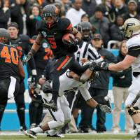 Photo -  Oklahoma State's Josh Stewart (5) leaps over Purdue's Frankie Williams (2) during the Heart of Dallas Bowl football game between Oklahoma State University and Purdue University at the Cotton Bowl in Dallas, Tuesday, Jan. 1, 2013. Oklahoma State won 58-14. Photo by Bryan Terry, The Oklahoman