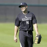 Photo - New York Yankees outfielder Carlos Beltran walks in the outfield during spring training baseball practice, Monday, Feb. 17, 2014, in Tampa, Fla. (AP Photo/Charlie Neibergall)