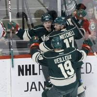 Photo - Minnesota Wild left wing Erik Haula, of Finland, celebrates his goal off Dallas Stars goalie Kari Lehtonen with teammates Torrey Mitchell (17) and Stephane Veilleux (19) during the first period of an NHL hockey game in St. Paul, Minn., Saturday, Jan. 18, 2014. (AP Photo/Ann Heisenfelt)