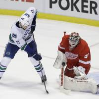 Photo - Detroit Red Wings goalie Jonas Gustavsson (50) of Sweden deflects a shot by Vancouver Canucks center Ryan Kesler (17) during the first period of an NHL hockey game in Detroit, Monday, Feb. 3, 2014. (AP Photo/Carlos Osorio)