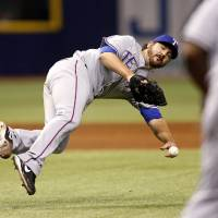 Photo - Texas Rangers pitcher Joe Saunders attempts a throw to first on a ball hit by Tampa Bay Rays' Yunel Escobar during the second inning of a baseball game Friday, April 4, 2014, in St. Petersburg, Fla. The throw went wide of first base and Escobar was awarded a single. (AP Photo/Mike Carlson)