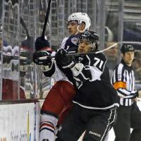 Photo - Los Angeles Kings center Jeff Carter (77) and Columbus Blue Jackets left wing Matt Calvert (11) slam into the boards in the first period of an NHL hockey game in Los Angeles Thursday, April 18, 2013. (AP Photo/Reed Saxon)