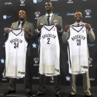 Photo - Brooklyn Nets players, from left, Kevin Garnett, Paul Pierce and Jason Terry, pose for photographers with their new jerseys during an NBA basketball news conference, Thursday, July 18, 2013 at Barlcays Center in New York. The  Nets introduced the trio they acquired in a blockbuster trade with the Boston Celtics. (AP Photo/Mary Altaffer)
