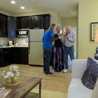 Photo - In this Friday, April 13, 2012 photo, Lennar Homes sales manager Joy Broddle, left, looks over a floor plan for the multi-generational home that is under construction for Kelly, center, and Bill Noorish while standing in the living area of the next-gen suite of a two-story model of a similar home, in Las Vegas. The Noorishes, who moved to Las Vegas recently from Pensacola, Fla., will be joined soon in their new home by their 32-year-old son and his wife. Builders across the country are revamping home designs to meet the needs of a growing number of Americans who are now living with extended family. The number of so-called multi-generational households where adults are living with their elderly parents or grown children has jumped since the Great Recession forced Americans to rethink living on their own.  (AP Photo/Julie Jacobson)
