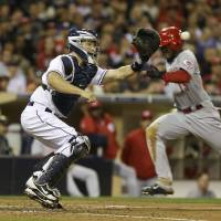 Photo - Cincinnati Reds' Derrick Robinson beats the throw and the tag by San Diego Padres catcher Nick Hundley while scoring from third on an infield ground ball in the fifth inning of a baseball game in San Diego, Monday, July 29, 2013.  (AP Photo/Lenny Ignelzi)
