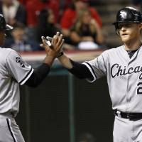 Photo -   Chicago White Sox's Dan Johnson, right, is congratulated by Dayan Viciedo after Johnson hit a two-run home run off Cleveland Indians starting pitcher David Huff in the fifth inning of a baseball game, Wednesday, Oct. 3, 2012, in Cleveland. Viciedo scored. (AP Photo/Tony Dejak)