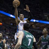 Photo - Oklahoma City Thunder's Russell Westbrook, top, shoots over Milwaukee Bucks' Brandon Jennings, left, Ersan Ilyasova, center, and Larry Sanders during the first half of an NBA basketball game on Saturday, March 30, 2013, in Milwaukee. (AP Photo/Tom Lynn)