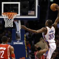 Photo - Oklahoma City's Kevin Durant goes up for a dunk over Houston's James Harden during Sunday's game.  Photo by Sarah Phipps, The Oklahoman