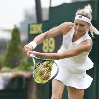 Photo - Maria Kirilenko of Russia plays a return to Sloane Stephens of U.S. during their first round match at the All England Lawn Tennis Championships in Wimbledon, London,  MondayJune  23, 2014. (AP Photo/Pavel Golovkin)