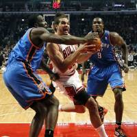 Photo - Chicago Bulls center Joakim Noah (13) drives the lane between Oklahoma City Thunder center Kendrick Perkins, left, and Serge Ibaka (9) during the first half of an NBA basketball game, Thursday, Nov. 8, 2012, in Chicago. (AP Photo/Charles Rex Arbogast) ORG XMIT: CXA106