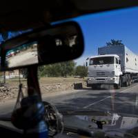 Photo - Trucks move towards a border control point with Ukraine in the Russian town of Donetsk, Rostov-on-Don region, Russia, Friday, Aug. 22, 2014. The first trucks of the Russian aid convoy crossed the Ukrainian inspection zone Friday morning. (AP Photo/Pavel Golovkin)
