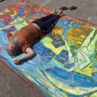 Photo - In this photo taken on April 4, 2013, Romanian artist Vasile Muresan, known as Murivale poses on one of his paintings in a parking lot,  in Bucharest, Romania. The white-bearded painter can often be seen sitting on his colorful canvasses which he displays in the street followed by the street dogs which are his companions and also inspire his work. The 56-year-old, whose home city is Bistrita_the Transylvanian town associated with the legendary Count Dracula_ has been painting with passion since he was a teen, producing vivid works of Monaco, the streets of Paris, the hurly burly of the Romanian capital and huge colorful more abstract canvasses. (AP Photo/Vadim Ghirda)