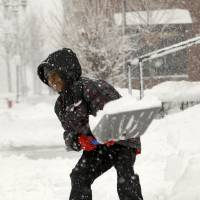 Photo - Seven-year-old Darius McDade shovels snow outside Morningside Baptist Church after services ended on Selby Avenue in St. Paul, Minn., on Sunday, Feb. 10, 2013. While nearby grown-ups around told him he didn't have to shovel, Darius said,