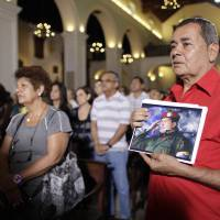 Photo - People, one of them holding an image of Venezuela's President Hugo Chavez, gather to pray for him at a church in Caracas, Venezuela, Monday, Dec. 31, 2012. Venezuela's President Hugo Chavez is confronting