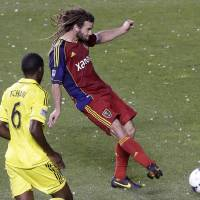 Photo - Real Salt Lake's Kyle Beckerman, right, scores as Columbus Crew's Tony Tchani (6) looks on in the second half of an MLS soccer game, Saturday, Aug. 24, 2013, in Sandy, Utah. Real Salt Lake defeated the Columbus Crew 4-0. (AP Photo/Rick Bowmer)
