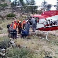 Photo - In this photo provided by the Poudre Fire Authority, search and rescue teams prepare to load a rescued hiker onto a medical evacuation helicopter Monday, Aug. 18, 2014, after a 16-year-old hiker fell and spent about three hours in a crevice near a popular hiking trail in northern Colorado. More than 40 people worked to pull the girl from the crevice on Horsetooth Rock in the Horsetooth Mountain Open Space on Monday. (AP Photo/Poudre Fire Authority)