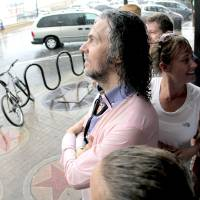 Photo - Flaming Lips lead singer Wayne Coyne seeks shelter from the weather at The Soundpony bar, 409 North Main Street, in downtown Tulsa during the Brady District Block Party.   BY NATHAN POPPE, THE OKLAHOMAN