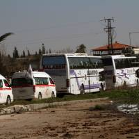 Photo - Some Syrian people on two buses followed by the Syrian Arab Red Crescent's vehicles evacuate Syria's battleground city of Homs, Friday, Feb. 7, 2014. Children, elderly women on wheelchairs and other civilians were evacuated Friday from besieged neighborhoods of Syria's battleground city of Homs under a deal struck between the government and the opposition that also included a three-day cease-fire allowing aid convoys to enter. (AP Photo)