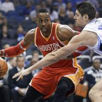 Photo - Houston Rockets' Dwight Howard, left, makes a move to get around Orlando Magic's Nikola Vucevic during the first half of an NBA basketball game in Orlando, Fla., Wednesday, March 5, 2014. (AP Photo/John Raoux)