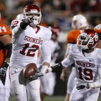 Photo - REACTION: Oklahoma's Austin Box (12) and Oklahoma's Demontre Hurst (19) react after an interception during the Bedlam college football game between the University of Oklahoma Sooners (OU) and the Oklahoma State University Cowboys (OSU) at Boone Pickens Stadium in Stillwater, Okla., Saturday, Nov. 27, 2010. Photo by Bryan Terry, The Oklahoman