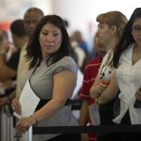 Photo - In this Tuesday, Jan. 15, 2012, photo,  Norma Urbario, left, and America Rodriguez stand in line, holding their resumes, during the job fair that the Miami Marlins hosted at Marlins Park in Miami. The number of Americans seeking unemployment aid jumped last week, though the increase mostly reflected difficulties the government has seasonally adjusting its numbers. Applications are still at levels signaling modest hiring. (AP Photo/J Pat Carter)