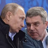 Photo - In this photo taken Saturday, March 8, 2014, Russian President Vladimir Putin, left, and International Olympic Committee President Thomas Bach speak during the ice sledge hockey match between Russia and South Korea of the 2014 Winter Paralympics in Sochi, Russia. (AP Photo/RIA-Novosti, Alexei Nikolsky, Presidential Press Service)