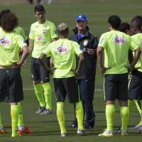 Photo - Brazil's coach Luiz Felipe Scolari, wearing a blue hat, gives instructions to his players during a practice session at the Granja Comary training center, in Teresopolis, Brazil, Monday, July 7, 2014. Brazil will face Germany on Tuesday in a World Cup semifinal match without Neymar. (AP Photo/Leo Correa)