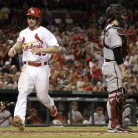 Photo - St. Louis Cardinals' Shane Robinson, left, scores on a single by Matt Carpenter as Arizona Diamondbacks catcher Tuffy Gosewisch stands by during the eighth inning of a baseball game Thursday, May 22, 2014, in St. Louis. (AP Photo/Jeff Roberson)