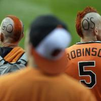 Photo -   Baltimore Orioles fans Tim Blaise, left, and his son Tim watch the Orioles take batting practice before Game 1 of the American League division baseball series against the New York Yankees on Sunday, Oct. 7, 2012, in Baltimore. (AP Photo/Patrick Semansky)