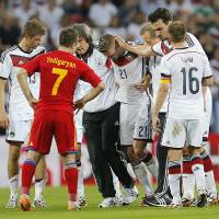 Photo - Germany's Marco Reus, center, leaves the pitch after he was injured during a soccer friendly match between Germany and Armenia in the Coface Arena in Mainz, Germany, Friday, June 6, 2014. (AP Photo/Michael Probst)