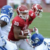 Photo - Indiana running back D'Angelo Roberts (20) is tackled by Indiana State's Travis Starks (7) during an NCAA college football game at Memorial Stadium in Bloomington, Ind., Saturday, Aug. 30, 2014. (AP Photo/The Herald-Times, Chris Howell)