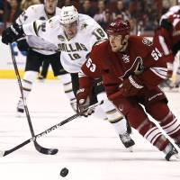 Photo - Phoenix Coyotes' Derek Morris (53) tries to keep the puck away from Dallas Stars' Reilly Smith (18) during the first period of an NHL hockey game Saturday, Feb. 2, 2013, in Glendale, Ariz. (AP Photo/Ross D. Franklin)