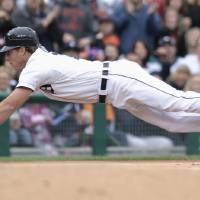 Photo -   Detroit Tigers' Andy Dirks dives into third base with a triple against the Minnesota Twins in the third inning of a baseball game Saturday, Sept. 22, 2012, in Detroit. (AP Photo/Duane Burleson)