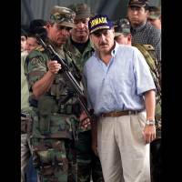 Photo -   FILE - In this May 1, 2001 file photo, Gen. Jorge Enrique Mora, left, holds a weapon used by suspected paramilitary fighters in Buenaventura, about 215 miles southwest of Bogota, Colombia. Mora spent a professional lifetime battling Colombia's rebels. On Monday, Oct. 15, 2012 he sits down with them to talk peace, and the former armed forces chief may be the key to whether the negotiations that open in the Norwegian capital of Oslo succeed or fail. Former Colombian President Andres Patrana is pictured at right. (AP Photo/Scott Dalton, File)