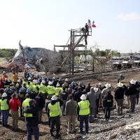 Photo - Workers pause for a memorial service at the site of the fire and explosion in West, Texas on Wednesday, April 24, 2013. The explosion at West Fertilizer which killed 14 people left a crater more than 90 feet (27 meters) wide and blasted the walls and windows off dozens of buildings in the town of 2,700. (AP Photo/The San Antonio Express-News, Tom Reel, Pool)