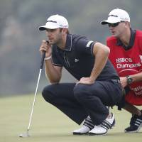 Photo - Dustin Johnson of the United States lines up for a putt with his caddie on the 3rd green during the final round of the HSBC Champions golf tournament at the Sheshan International Golf Club in Shanghai, China, Sunday, Nov. 3, 2013. (AP Photo/Eugene Hoshiko)