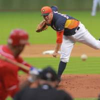 Photo - Houston Astros pitcher Brett Oberholtzer throws to Rojos del Aguila de Veracruz's Enrique Osorio during the first inning in a spring exhibition baseball game on Saturday, March 29, 2014, in Houston.(AP Photo/Richard Carson)