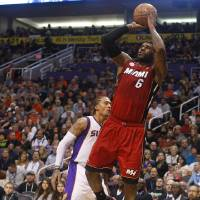 Photo -   Miami Heat forward LeBron James (6) draws the foul and scores on Phoenix Suns forward Michael Beasley (0) in the second quarter during an NBA basketball game on Saturday, Nov. 17, 2012, in Phoenix. (AP Photos/Rick Scuteri)