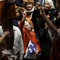 Photo -   Edith Royal, wife of Darrell K. Royal, center, holds up the Hook'em horns as the