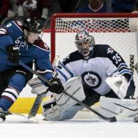 Photo - Colorado Avalanche center Matt Duchene (9) reaches for the puck in front of Winnipeg Jets goalie Al Montoya (35) during the second period of an NHL hockey game in Denver on Sunday, Dec. 29, 2013. (AP Photo/Joe Mahoney)