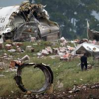 Photo - FILE - In this Aug. 14, 2013, file photo, a investigator looks through debris of a UPS A300 cargo plane after it crashed on approach at Birmingham-Shuttlesworth International Airport in Birmingham, Ala. Federal investigators are looking at pilot fatigue, among other issues, as a possible factor in the fatal predawn crash of a UPS cargo jet. The National Transportation Safety Board scheduled a hearing for Feb. 20, 2014, on the accident, which killed both pilots. (AP Photo/Hal Yeager, File)