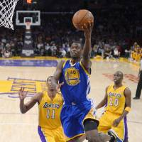 Photo - Golden State Warriors forward Harrison Barnes, center, goes up for a shot as Los Angeles Lakers forward Wesley Johnson, left, and guard Jodie Meeks defend during the first half of an NBA basketball game, Friday, April 11, 2014, in Los Angeles. (AP Photo/Mark J. Terrill)